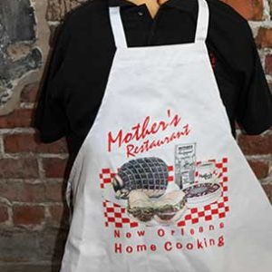 """black polo tshirt wearing a white apron with Mothers restaurant"""" and """"New Orleans Home cooking"""" red print and an image of foods printed on the apron"""